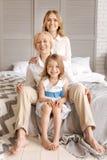 Reizende Großfamilie, die ein hinter anderen sitzt Stockfotografie