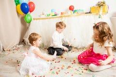 Reizende hübsche Kinder spielen auf dem Boden Stockbild