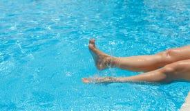 Reizende, herrliche, sexy weibliche Füße, Wasser spritzt und Türkispoolwasser lizenzfreies stockbild