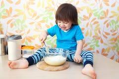 Reizende 2 Jahre Junge kocht das Sitzen auf einer Tabelle Stockbild