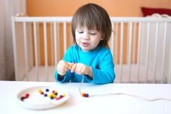 Reizende 2 Jahre Junge spielt mit Perlen von verschiedenen Farben Stockfotografie