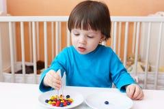 Reizende 2 Jahre Junge spielt mit Scheren und Perlen zu Hause Lizenzfreie Stockfotos