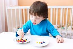 Reizende 2 Jahre Junge spielt mit Scheren und Perlen zu Hause Educati Lizenzfreies Stockbild
