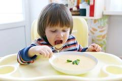Reizende 2 Jahre kleine Junge, die Gemüsesahnesuppe essen Stockbilder