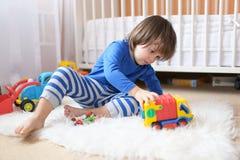 Reizende 2 Jahre Kleinkindjunge spielt Autos zu Hause Stockfotos