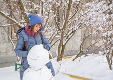 Reizende Jugendliche sculpts einen Schneemann Lizenzfreies Stockfoto