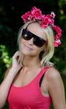 Reizende junge blonde Dame mit Girlande von Blumen Stockbild