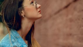 Reizende junge Blondine mit den roten Lippen, die an der Backsteinmauer aufwerfen stock footage