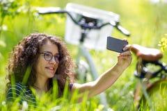 Reizende junge Brunettefrau, die ein selfie in einem Park nimmt stockfotografie