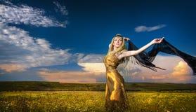 Reizende junge Dame, die drastisch mit langem schwarzem Schleier auf grünem Feld aufwirft Blondine mit bewölktem Himmel i Lizenzfreie Stockbilder
