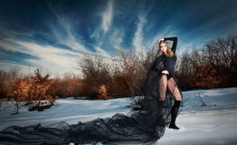 Reizende junge Dame, die drastisch mit langem schwarzem Schleier in der Winterlandschaft aufwirft. Blondine mit bewölktem Himmel i Stockbild