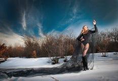 Reizende junge Dame, die drastisch mit langem schwarzem Schleier in der Winterlandschaft aufwirft Blondine mit bewölktem Himmel i Stockbild