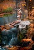 Reizende junge Dame, die nahe Fluss in verzaubertem Holz sitzt Sinnliche Blondine mit der weißen Kleidung, die provozierend im he Stockbild