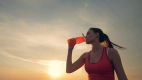 Reizende junge Dame trinkt beim im Freien laufen stock video