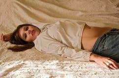Reizende junge Frau auf Bett Stockfotos