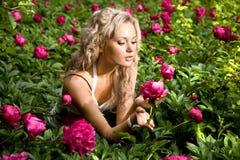 Reizende junge Frau, die auf einem Garten sich entspannt Stockfoto