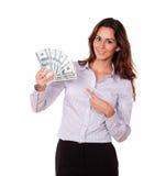 Reizende junge Frau, die Bargelddollar hält Stockfoto