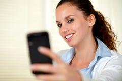 Reizende junge Frau, die eine Meldung mit Mobile sendet lizenzfreie stockbilder