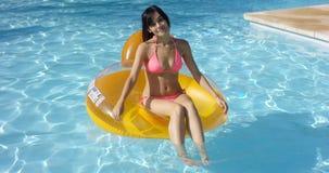 Reizende junge Frau, die in einen Swimmingpool schwimmt Stockfoto
