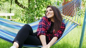 Reizende junge Frau, die Ferien liegen in einer Hängematte, glückliches Mädchenlächeln genießt stock video