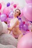 Reizende junge Frau, die mit Ballonen aufwirft Stockbilder