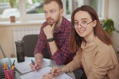 Reizende junge Jugendliche, die an einem Projekt mit ihrem Lehrer arbeitet stockfoto