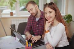 Reizende junge Jugendliche, die an einem Projekt mit ihrem Lehrer arbeitet stockfotografie