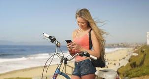 Reizende junge Kalifornien-Frau an simsendem Fahrradinhaber des Strandes zu Stockbilder