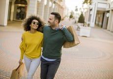 Reizende junge multiethnische Paare mit Taschen im Einkaufen lizenzfreie stockfotos