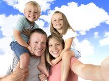 Reizende junge Paare, die selfie Fotoselbstporträt mit Stock und tragendem Sohn und Tochter des Handys auf den Schultern aufwerfe Stockfotos