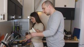 Reizende junge Paare, die zusammen Teller lächeln und waschen und abwischen stock video