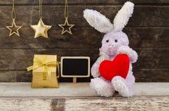 Reizende Kaninchenpuppe, die das rote Herz sitzt nahe Geschenkbox hält Stockfotografie