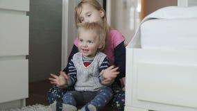 Reizende Kinder sitzen auf dem Boden und klatschen ihre Hände stock video