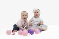Reizende Kleinkinder, die mit bunten Bällen spielen Stockfotos