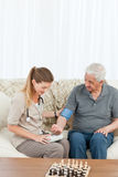 Reizende Krankenschwester, die ihrem Patienten hilft, Übungen zu tun Lizenzfreie Stockbilder