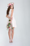 Reizende lächelnde Frau in den Rosen winden versteckenden Blumenstrauß von Blumen Lizenzfreie Stockfotos