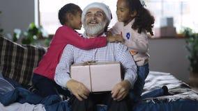 Reizende Mädchen, die dem Großvater einen Kuss am Weihnachten geben stock video footage