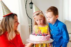 Reizende Mädchen- und Jungenzwillinge in den Parteihüten brennen heraus vier Kerzen auf einem Geburtstagskuchen durch Mutter läch stockfotografie