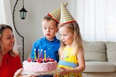 Reizende Mädchen- und Jungenzwillinge in den Parteihüten macht einen Wunsch vor Schlag vier Kerzen auf einem Geburtstagskuchen au lizenzfreie stockfotos
