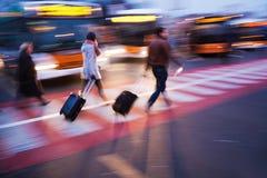 Reizende mensen bij een busstation Stock Afbeeldingen