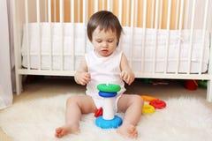 Reizende 18 Monate Baby spielt Verschachtelungsblöcke Stockfoto
