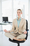 Reizende noble Geschäftsfrau, die in Lotussitz auf ihrem Drehstuhl meditiert Stockbild