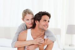 Reizende Paare, die auf ihrem Bett umarmen Stockfoto