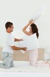 Reizende Paare, die einen Kissenkampf auf ihrem Bett tun stockfotos