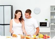 Reizende Paare, die zusammen ihr Frühstück zubereiten Stockfoto