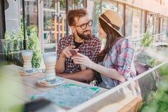 Reizende Paare sitzen zusammen und betrachten einander Sie hält Telefon in den Händen Er zeigt auf es Sie lächeln miteinander lizenzfreie stockfotografie