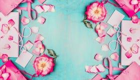 Reizende rosa Blumen mit den Blumenblättern und den rosa Papiereinkaufstaschen auf hellblauem Hintergrund, Draufsicht, Fahne Lizenzfreies Stockfoto