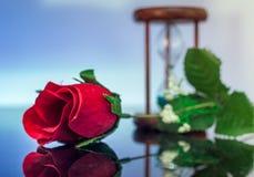 Reizende rote Rosen-Blume, die über Glastisch mit der Sanduhr zeigt im Hintergrund nachdenkt Stockfotos