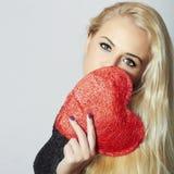 Reizende schöne blonde Frau mit rotem Herzen. Schönheits-Mädchen. Halten Sie Liebes-Symbol. Valentinstag. im schwarzen Kleid Stockfoto
