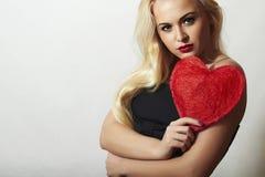 Reizende schöne blonde Frau mit rotem Herzen. Schönheits-Mädchen. Zeigen Sie Liebes-Symbol. Valentinstag. Schwarzes Kleid Lizenzfreie Stockfotos
